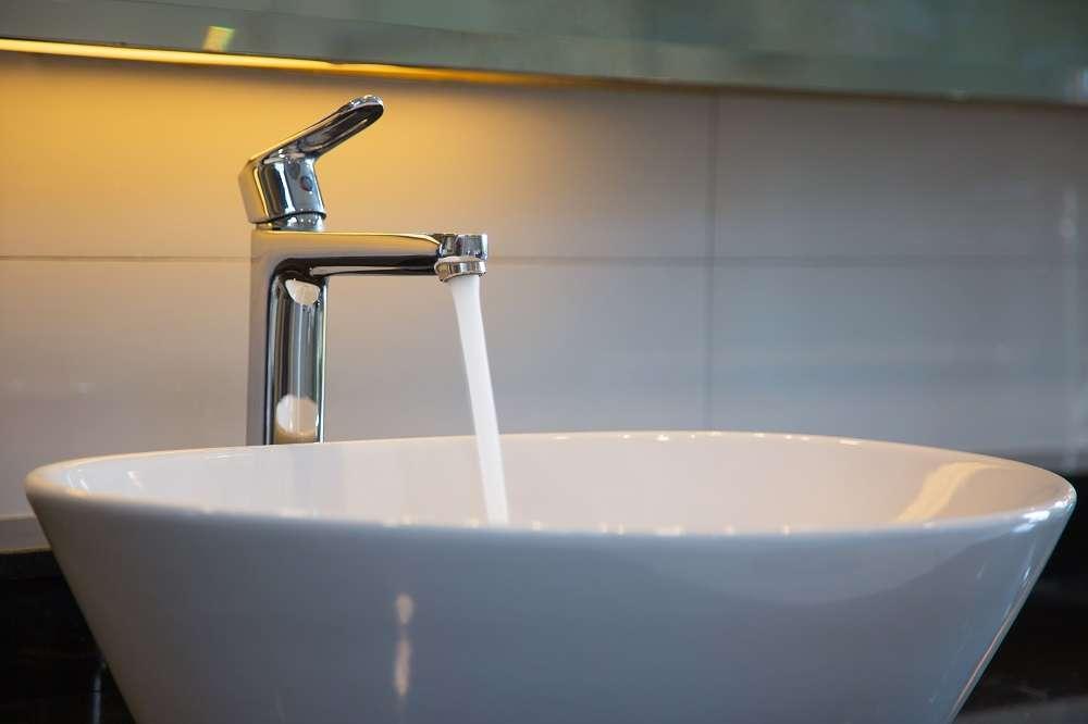 Torneira de banheiro aberta para troca da água e limpeza dos canos após limpeza de caixa d